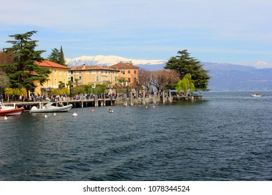 SALO, ITALY - APRIL 2, 2018: salo harbour in salo on the background of the alps, salo, lombardy, italy