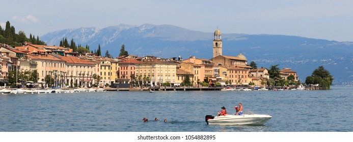 Salo, Italy - August 8, 2018: Townscape of Salo and tourists on a boat with mountain panorama at Lake Garda. The city Salo was the seat of government of the Italian Social Republic from 1943 to 1945.