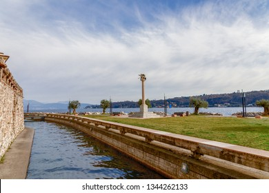 SALO, ITALY - FEBRUARY 24, 2019: Beautiful view of the canal and Lake Garda in the city of Salo (Salò). In the center of composition is the symbol of city the Winged Lion.  Lombardy region, Italy