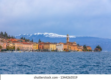 SALO, ITALY - FEBRUARY 24, 2019: Panoramic view of the city Salo (Salò) and the embankment on Lake Garda. In the background are snowy Alps. Winter period.  Lombardy region, Italy