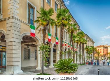 SALO, ITALY - JUNE 1: Italian flags on the facade of Palazzo della Magnifica Patria, iconic building in the town of Salo, Lake Garda, Italy, June 1, 2014
