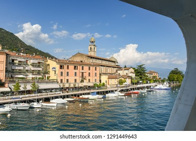 SALO, ITALY - SEPTEMBER 2018: Lakefront of the town of Salo on Lake Garda with view framed by the window of a ferry.