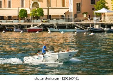 SALO, LAKE GARDA, ITALY - SEPTEMBER 2018:  People on a small motor boat at speed near the lakeside in Salo on Lake Garda.