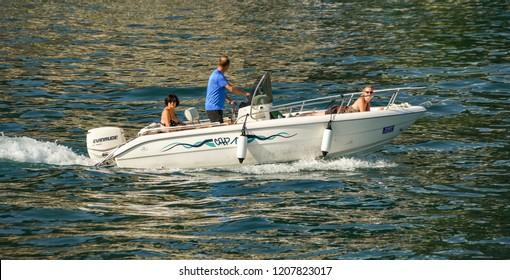 SALO, LAKE GARDA, ITALY - SEPTEMBER 2018:  People on a small motor boat near the lakeside of Salo on Lake Garda.