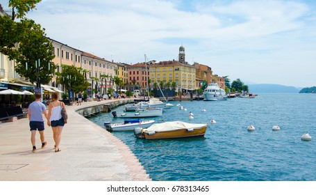 Salo on the Garda lake (Lago di Garda) in Italy, Europe. With a romantic couple walking by waterfront.