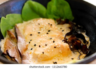 Salomon with fish with green and dark leaves served with sauce - plate close-up