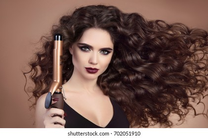 Salon Beauty. Curly hair. Close-up of brunette girl with blowing hairstyle holding Professional curling iron. Marsala eye shadow makeup. Glamour female isolated on beige background.