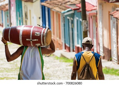 Salsa musician carrying a conga while walking with a friend in the streets of Trinidad Cuba