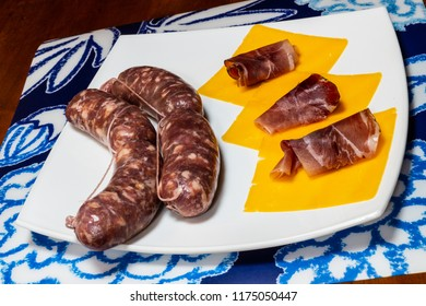 Salsiccia, made by minced meat inside a gut, cheddar and speck of Tyrol on a dish.