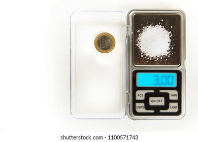 Salt in amount of 3 grams on small digital scale comparing with one euro coin