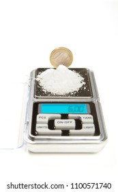 Salt in amount of 6 grams on small digital scale comparing with one euro coin