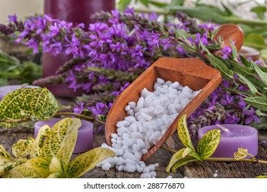 salt bath in wooden spoon with flowers and  leaves in background