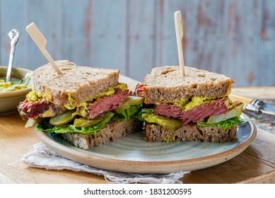 Salt beef sandwich with pickled cucumber and mustard tartar sauce cut in half