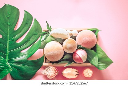 salt bombs for a spa bath still life on a colored background with tropical real leaves