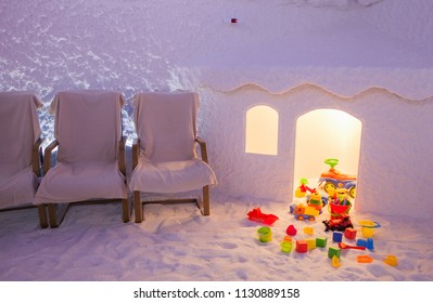 salt cave interior with textured walls, warm colored lighting, chairs and children's playhouse.