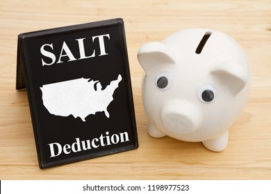 The SALT deduction for the federal USA taxes, A piggy bank with retro freestanding chalkboard on a wood desk with text SALT deduction and a map of the USA