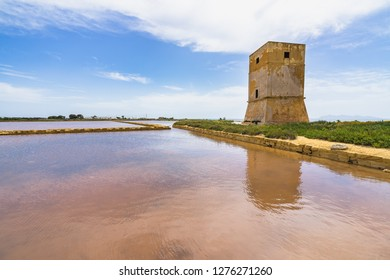 Salt evaporation pond and Nubia tower at salt flats near Trapani, Sicily, Italy