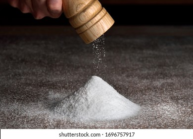 Salt falls from the grinder on a table full of salt. Hand holding salt grinder, heap of salt. Detail on grinder and saltpyramid.