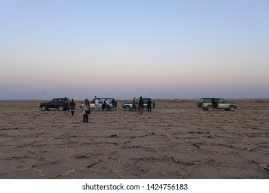 Salt Field, Kashan, Iran - October 2017 : A group of cars with tourists parking on the salt field in Kashan during a sunset.