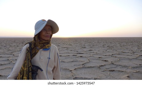 Salt Field, Kashan, Iran - October 2017 : An elderly asian female tourist standing at a salt field during a sunset near Kashan, Iran.