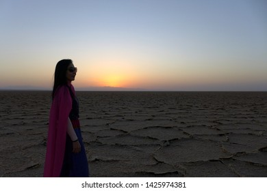 Salt Field, Kashan, Iran - October 2017 : An asian female tourist standing at a salt field during a sunset near Kashan, Iran.