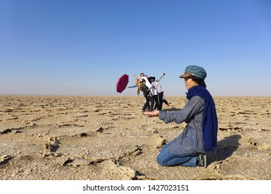 Salt field, Kashan, Iran - October 2017 : A group of asian tourists are acting giant and dwarfs for taking photo at a salt field near Kashan, Iran.