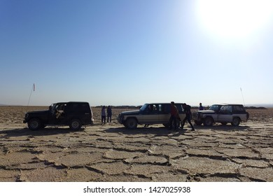 Salt Field, Kashan, Iran - October 2017 : A group of cars with tourists parking on the salt field in Kashan under a strong sun.