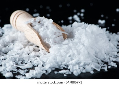 Salt flakes and wooden scoop on black background