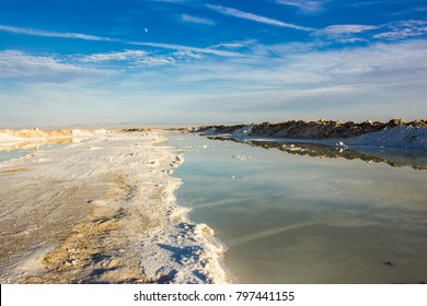 Salt flat with water pool reflecting the blue sky and moon