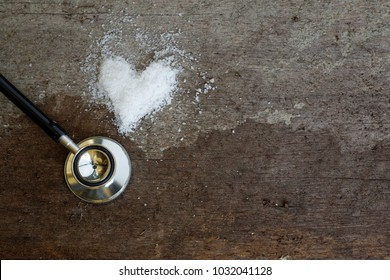 Salt forming heart shape with stethoscope on wooden background. Conceptual