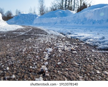Salt grains on icy sidewalk surface in the winter. Applying salt to keep roads clear and people safe in winter weather from ice or snow, closeup view