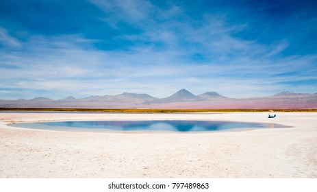 Salt Lagoon at Salt Flats in Desert with view of Andes Mountains on Horizon (Atacama, Chile).