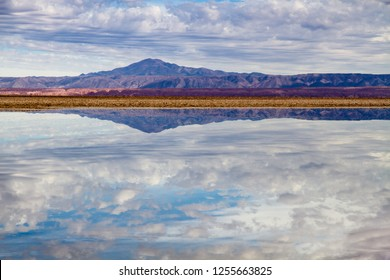 """Salt lagoon in the """"Salar de Atacama"""" landscape view in the Atacama Desert in Chile, with mountains and volcano reflections on the still water of the lake."""