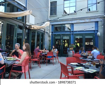 Salt Lake City, UT - 3 July 2018: People sitting outside eating and drinking enjoying a summer day on the outdoor back patio of Squatters Pub, a local bar, in downtown Salt Lake City, Utah.
