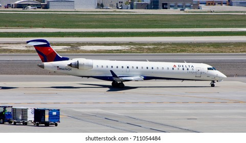 SALT LAKE CITY, UTAH – April 16, 2016: A Bombardier CRJ-700 of SkyWest Airlines, operating as Delta Connection, taxies to the runway for departure at Salt Lake City International Airport.