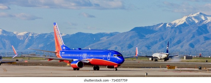 SALT LAKE CITY, UTAH – April 16, 2016: A Southwest Airlines Boeing 737-800 taxies to the runway while a Delta Air Lines Boeing 737-800 lands at Salt Lake City International Airport.