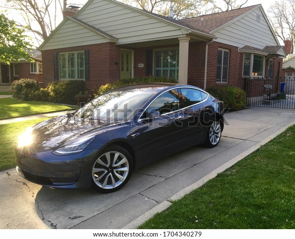 Salt Lake City, Utah, April 2019.  A 2019 midnight metallic silver Tesla Model 3 sits in the driveway of a beautiful, red brick home in the Sugarhouse neighborhood with sunlight glare.