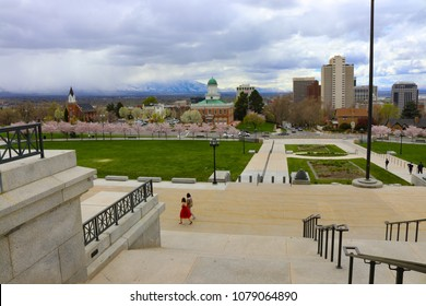 Salt Lake City, Utah State Capitol steps with city skyline and a girl, woman, in a red dress.  Looks like they were taking pictures of her in her prom dress.