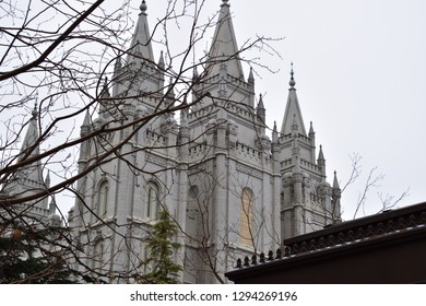 Salt Lake City, Utah / U.S.A. - January 19th 2019: Salt Lake Temple downtown on a downcast day with bare tree branches in view