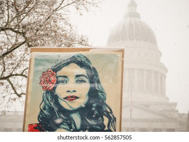 Salt Lake City, Utah, USA - 23rd January, 2017. Marchers walk up State Street in the snow with the Women's March in Salt Lake City, Utah with a sign by the artist Shepard Fairey in the foreground.