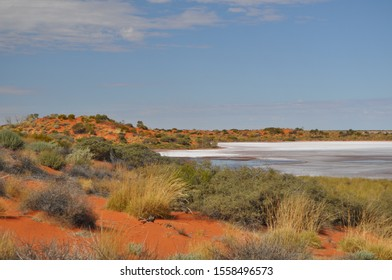 Salt lake on the Canning Stock Route Western Australia fringed by red sands and desert vegetation