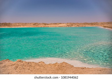 Salt lake with turquoise water and white salt on the shore near Siwa oasis, Egypt
