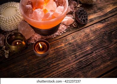 Salt lamp of pink Himalayan salt on vintage wooden background