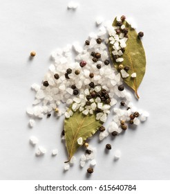 Salt and mix of pepper with bay leaves on white background. Top view.