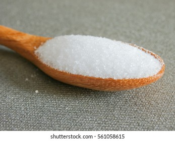 Salt on wooden spoon with grey fabric background.