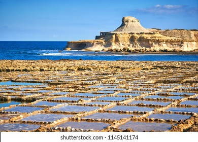 Salt pans and a rocky mountain near Zebbug town at Gozo island, Malta