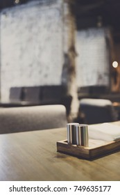 Salt and pepper bottles on wooden table. Spices on empty dining place, blurred restaurant interior on background, copy space