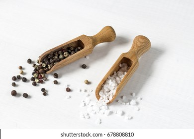 salt and pepper. salt crystals and pepper corns on wooden spoons