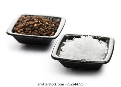 salt and pepper into black bowls, on white background