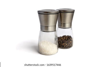 Salt and pepper mill set. Isolated on white. Glass and stainless steel grinders. Filled with coarse white salt grind and whole black peppercorn. Isolated on white, copy space.